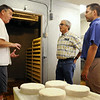 Kieth Adams, owner of Alemar Cheeses (left), explains the cheese-making process to Rep. Clark Johnson (center) and Charlie Poster, an assisistant commissioner with the Minnesota Department of Agriculture on Monday. Photo by John Cross