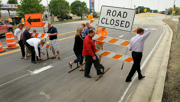 Representives from the various businesses most affected by the construction of the roundabout at Adams Street and Highway 22 remove the barricades to officially open it up to traffic at about 6 p.m. on Friday. Photo by John Cross