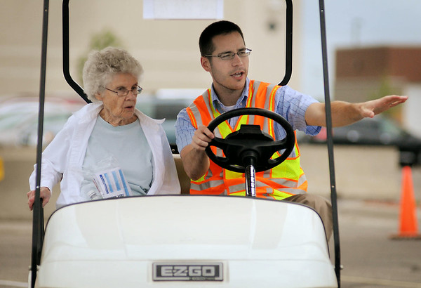 Zachary Tess, an engineer with the Minnesota Department of Transportation, gives some pointers to Thelma Siegfried of North Mankato, while driving a golf cart through a scaled-down roundabout mock-up during a Roundabout Fair in the Gander Mountain parking lot on Thursday. The roundabout at Highway 22 and Adams Street will open today at 6 p.m. Photo by John Cross