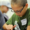 Cooper Thomez ponders solutions to a coin puzzle at Minnesota State University's ZAP camp. The camp which concludes today had students exploring the roles of mathematics in everyday life. Photo by John Cross