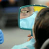 A patient checks out a new smile after receiving a partial dental appliance on Saturday at the Mission of Mercy. Photo by John Cross