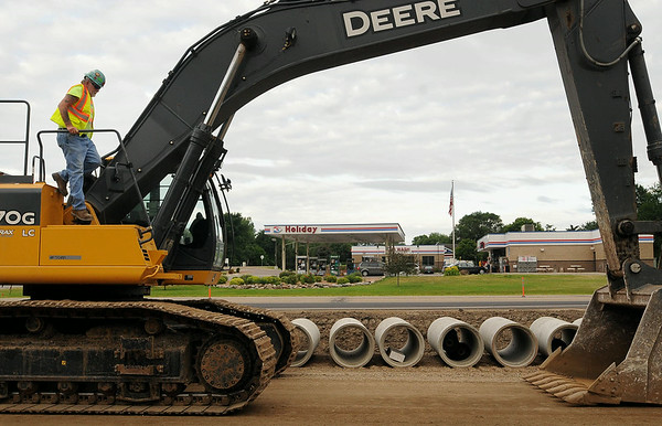 Mike Stolz of Truman, a heavy equipment operator with Hoffman Construction, readies his backhoe for work on Highway 169 north of St. Peter. The Holiday gas station and several other businesses will be directly affected by a MnDOT proposal to close a section of the highway down completely and detouring traffic to nearby Old Minnesota Avenue for three to four weeks during rebuilding of the roadway. Photo by John Cross