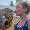 Anika Sathoff, 7, kisses the winning sheephead carp caught earlier in the day at Paddlefish Days held in Madison Lake. Anika, from Madison Lake, thought that she would not be able to kiss the fish, as she came in second in the voting, but Paddlefish Days workers surprised her at the last second and announced that she could kiss the fish. Photo by Jackson Forderer