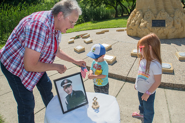 Esther Ewert (left) gives out American flags to Abraham Ashmore, 2, and Stella Ashmore, 4, before the start of a family gathering that honored David Fasnacht's service in the Vietnam War. Fasnacht died in 1967 in the war and family members gathered at the memorial on the 50th anniversary of his death. Abraham and Stella are David's great nephew and great niece. Photo by Jackson Forderer