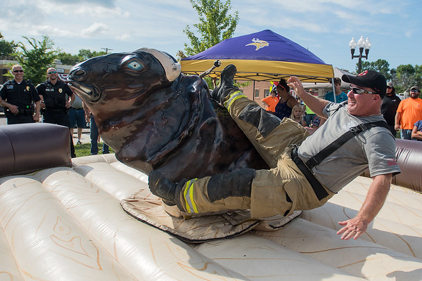 "Madison Lake Fire Chief Kevin Kennedy falls off a mechanical bull at Paddlefish Days in a friendly competition that pitted the fire department versus the police department. ""Let's get this straight,"" Kennedy said after falling off the bull, ""I stayed on longer than the police chief."" Photo by Jackson Forderer"