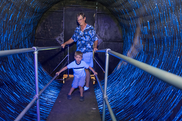 Steve Bixenman walks through the vortex tunnel with his grandson Max Ahern, 5, at the Blue Earth County Fair in Garden City on Saturday. The tunnel is a part of Northern Frights, a company that will be running a 3D haunted house on the fairgrounds in October. Photo by Jackson Forderer