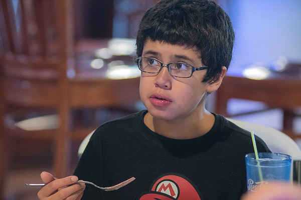 Charley Solano, 14, listens to family members at his 10th anniversary heart transplant party held at the Wow! Zone on Tuesday. The family knew from birth that Charley had a heart defect and said his body has not rejected the new heart. Photo by Jackson Forderer