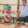 Randy Dinsmore (right) supervises Nathan Putrah, 11, as he shaves down a piece of wood at the Blue Earth County Historical Society building on Saturday. Dinsmore and David Mauch are planning to build a log cabin in the style of the Holberg cabin from the 19th century with help from younger fairgoers. Photo by Jackson Forderer