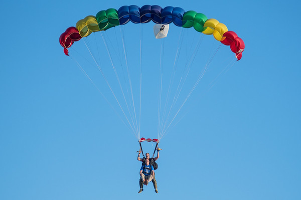 Damon Brunow (bottom) puts his feet up as Jason Petterson steers their parachute towards the landing zone at Mankato Airport on Wednesday. Brunow and other Wal Mart employees skydived on Wednesday to raise funds for the Children's Miracle Network. Photo by Jackson Forderer