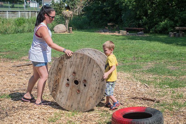 Natalie (left) rolls a big spool with her son and Brayden Stenzel, 4, at the new Adventure Park in Eagle Lake on Thursday. Stenzel said her girls discovered the park when they moved to town from Mankato. It was Brayden's first time visiting the park. Photo by Jackson Forderer