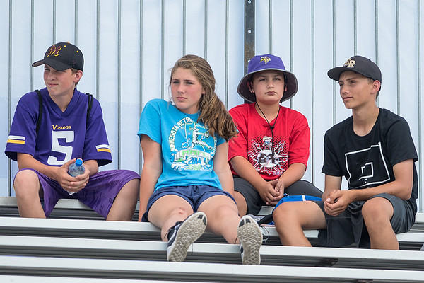 "From left, Jake Sizer, 13, Abby Stierlen, 13, Derek Stierlen, 11 and Blake Ritzer, 15, watch a Vikings practice from one of the two large grandstands set up by the practice fields at Minnesota State. ""There is a lot of waiting around,"" Jake said of collection autographs. Photo by Jackson Forderer"