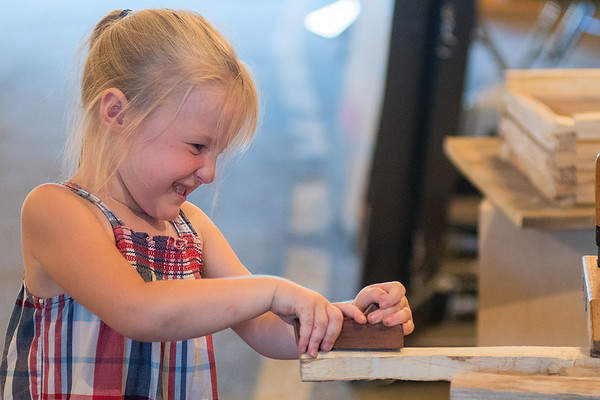 Evelynn Langworthy, 4, from Mapleton shaves down a piece of wood in the Blue Earth Historical Society building at the Blue Earth County Fair on Saturday. The booth was set up to teach children how to use tools from the 1800s. Photo by Jackson Forderer