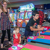 Charley Solano (right), 14, plays Skee Ball with his half-sister Rachel Hess (left), 18, and his nephew Jacob Johnson, 2, at the Wow! Zone during the 10th anniversary of his heart transplant. After being born with a heart defect, Charley had three surgeries before receiving a heart transplant at Mayo Hospital. Photo by Jackson Forderer