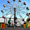 A boy rides through downtown Minnesota Lake as he waits for the midway rides to open at Festag Tuesday afternoon.