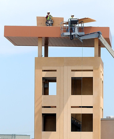 Workers unload plywood atop the fire training tower while working on the addition to Mankato's Law Enforcement Center Thursday.