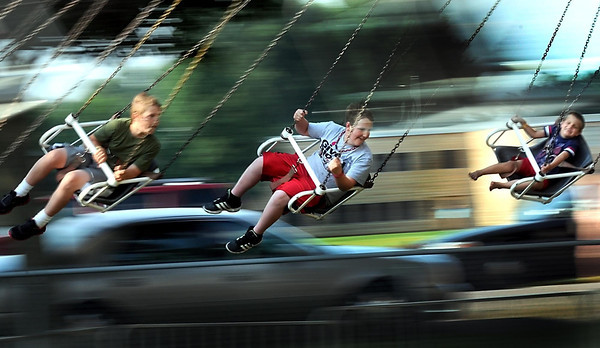 Pat Christman<br /> Kids streak around in swings on the Zumur at the North Mankato Fun Days midway Wednesday evening.