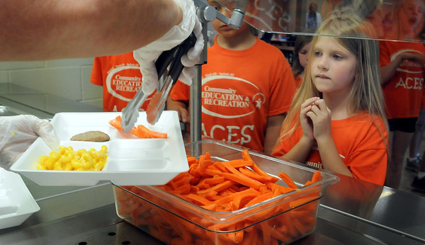 John Cross<br /> Youngsters participating in Aces, a summer recreation program at Rosa Parks Elementary School, line up for lunch that in addition to kid favorite mac-and-cheese, included turkey sausage, fruit and fresh carrots.