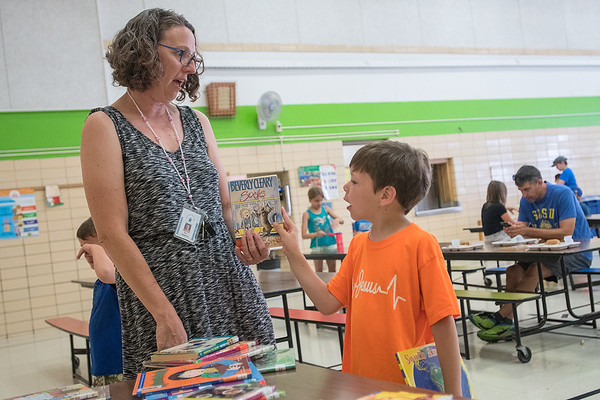"""Jonah Williams (right), 6, takes a book recommended to him by Roosevelt Elementary principal Ann Haggerty as she gave books away to students on her birthday. Haggerty said that the books were donated by parents and teachers, and added, """"I love my summer but I miss the kids."""" Photo by Jackson Forderer"""