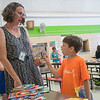 "Jonah Williams (right), 6, takes a book recommended to him by Roosevelt Elementary principal Ann Haggerty as she gave books away to students on her birthday. Haggerty said that the books were donated by parents and teachers, and added, ""I love my summer but I miss the kids."" Photo by Jackson Forderer"