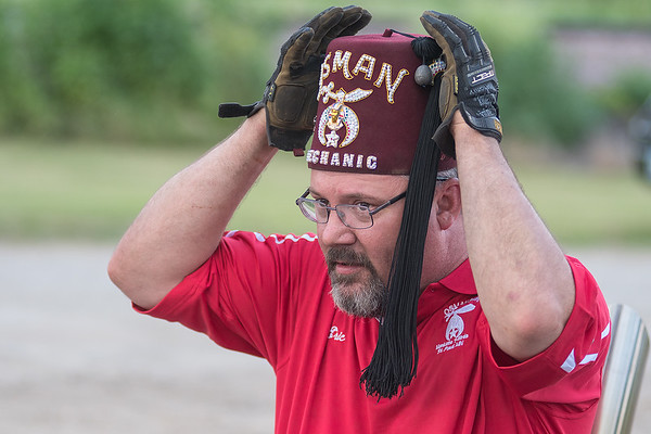 Eric Mundt of the Mankato Shriners puts on his fez before riding in Minnesota Lake's Festag parade on Wednesday. Photo by Jackson Forderer