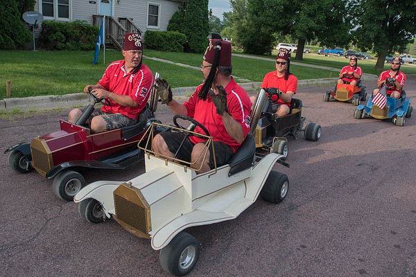 Eric Mundt (center) shows fellow Shriner Mike Jacobs how his go-kart moves forward without pressing the gas pedal as the Shriners lined up for Minnesota Lake's Festag parade on Wednesday. Photo by Jackson Forderer