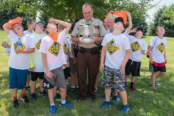 Participants in the 29th annual Safety Camp gather around  Nicollet County Sheriff Jason Mediger as he flies a drone during a demonstration as part of the camp. Photo by Jackson Forderer