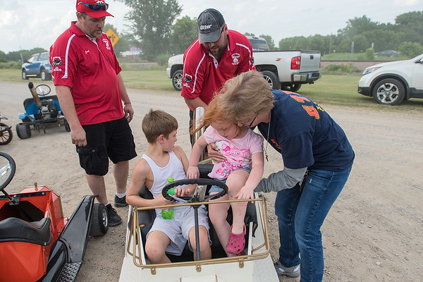 Annette Birr (right) puts Briella Brandt, 3, inside one of the Shriners go-karts with Chase Birr, 9, as Brock Petersen (back right) and Jared Juliar (left) work on filling up the kart with gas before the start of Minnesota Lake's Festag parade. Photo by Jackson Forderer