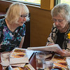 Former Bell Tower School teacher Ginger Kettwig (right), who was known by students as Ms. Ruble, looks over yearbook photos with Elaine Tosch at a small gathering of Bell Tower students at Baker's Square on Monday. Photo by Jackson Forderer