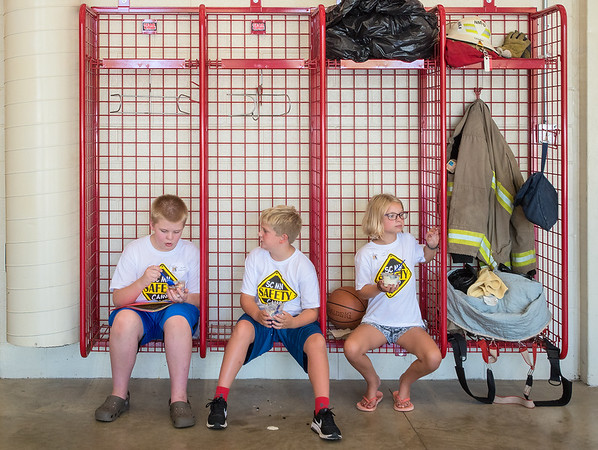 From left, Derek Edmunson, 12, Sammy Parker, 9, and Lola Jones, 9, have their afternoon snack, Culver's frozen custard, while sitting in empty firemen lockers at North Mankato Fire Station No. 2 during Safety Camp. Photo by Jackson Forderer