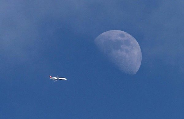 A commercial jet flies past the moon over Mankato Wednesday. The first jet airliners hadn't been in service for a decade when President John F. Kennedy suggested in 1961 that America should put a man on the moon. Eight years later, and 50 years ago this week, Neil Armstrong and Buzz Aldrin set foot on the lunar surface.