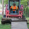 Ben Hebl tears up an old sidewalk along Commerce Drive on Wednesday that will be replaced with a wider bike and pedestrian path.