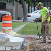 Karen Kline sprays a new curb along Commerce Drive as the construction project continued on Wednesday.