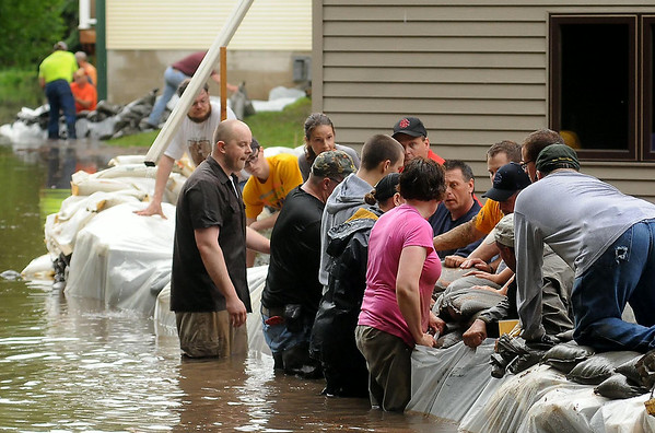 Volunteers place sandbags to protect homes in St. Clair from the nearby rising Le Sueur River on Thursday.<br /> Photo by John Cross