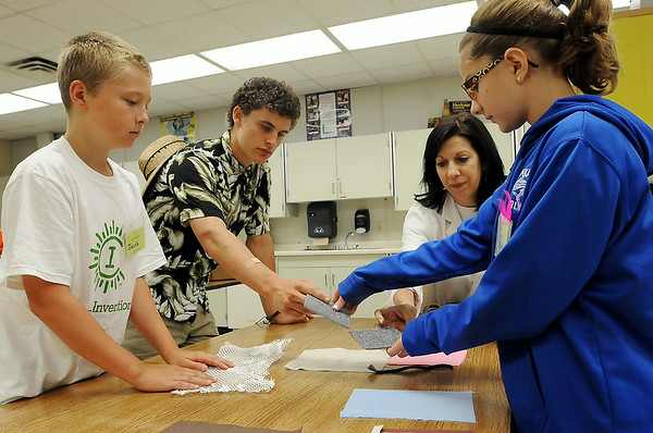 Instructor Marcy Koch and counselor William Cipor assist  campers Josh Arndt (left) and Sarah Yenish (right) with a and exercise on fabric textures at Camp Invention at East High School this week. Photo by John Cross
