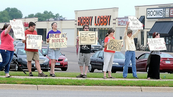 Protesters hold up signs near the Mankato Hobby Lobby store Saturday. The local chapter of National Organization of Women organized the protest over the recent Supreme Court rulling that allows employers to ban certain kinds of contraceptives from their health plans if if violates religious beliefs. Photo by Pat Christman
