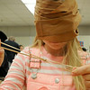 Blindfolded camper Emily Krueger, one of a bout 60 youngsters attending Camp Invention at East High School this week, attempts to make a bracelet of rubber bands as part of a tactile/texture exercise. Photo by John Cross