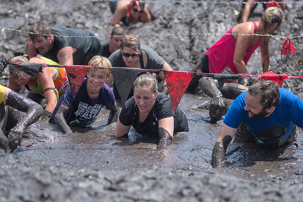 Participants in the Warrior Dash crawl through the mud under barbed wires as the last obstacle on the course. The Warrior Dash, a fundraiser for St. Jude Hospitals, was held at the Caribou Gun Club in rural Le Sueur. Photo by Jackson Forderer