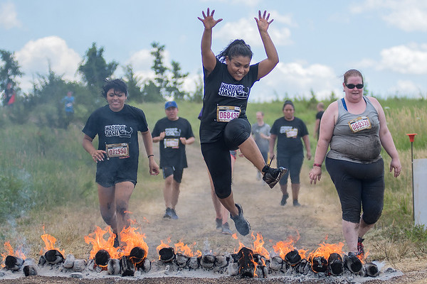 Lizbeth Herrera (center) jumps over a fire obstacle during the Warrior Dash race held on Saturday at the Caribou Gun Club in rural Le Sueur. Participants jumped over fire, crawled through mud, swam through water, and climbed ropes to finish the race. Photo by Jackson Forderer