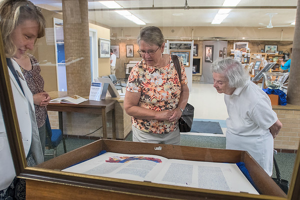 Shelley Harrison (left) lets Audrey Splinter (center) and others view the St. John's Bible before locking the glass case after it was opened for the media at the Blue Earth County Historical Society. The St. John's Bible exhibit will be on display until Sept. 1. Photo by Jackson Forderer