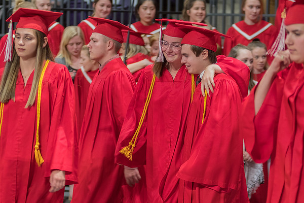 Cameron Grund (center) puts her arm around Tyler Qualley as the two walked off the choir stage, singing for the last time with the Mankato West choir during Wednesday's commencement ceremony held at Bresnan Arena. Photo by Jackson Forderer