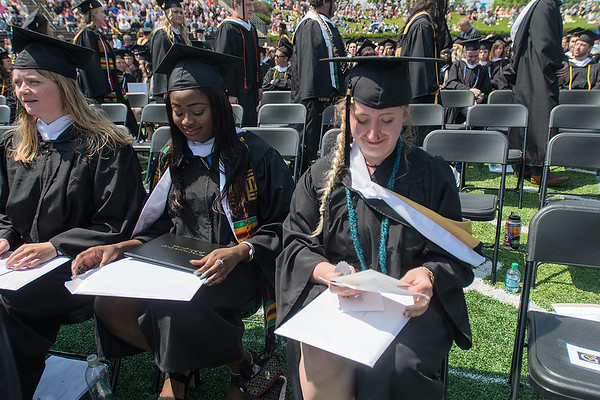 Madison Adams looks over her graduation materials with a smile as other Gustavus Adolphus graduates lined up to receive their degrees on Saturday. Photo by Jackson Forderer