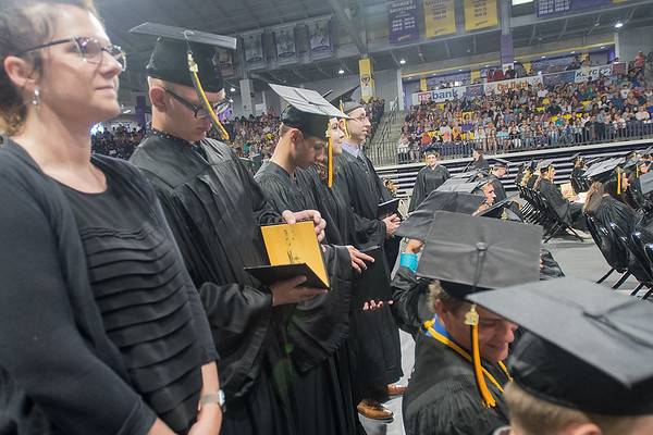 Mason Schutz (second from left) and other Mankato East graduates take a quick peak at their diploma during commencement ceremonies held at Bresnan Arena on Wednesday. Photo by Jackson Forderer