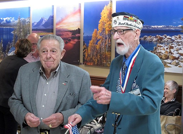 Pearl Harbor survivor Charles T. Sehe, 92, of Mankato (right) and Nevada Veterans Services Commissioner Chuck Harton speak to the crowd that greeted Sehe in October 2015 at Reno-Tahoe International Airport. Sehe was nearly killed on board the USS Nevada during the attack on Pearl Harbor and continued to serve on the battleship when it aided in the invasions at Normandy and Iwo Jima during World War II. So at age 92, he decided it was time to make his first visit to the state the ship was named after. Photo by The Associated Press