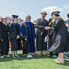 Professors with the Department of Math, Computer Science and Statistics shake hands with a graduate at Gustavus' commencement ceremony held at Hollingsworth Field Photo by Jackson Forderer