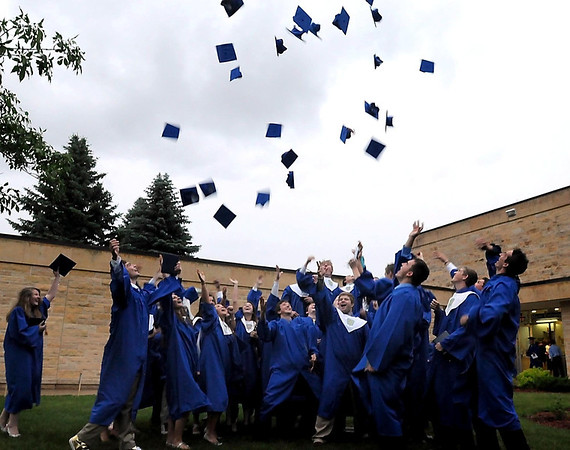 Graduates from Mankato Loyola high school throw their mortarboards in the air after the school's graduation ceremony Wednesday.