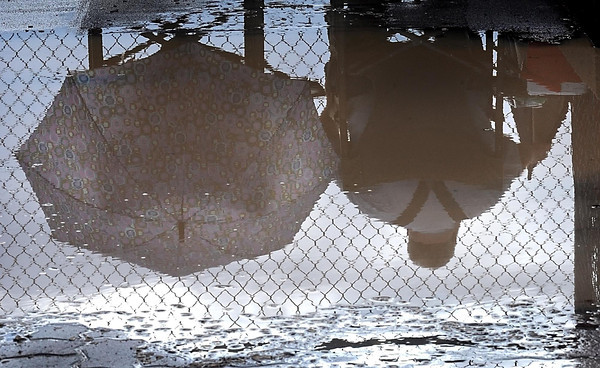Pat Christman<br /> A couple waits out a rain delay during a section championship softball game Thursday at Caswell Park in North Mankato.