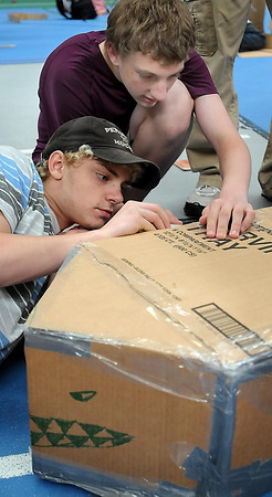 John Cross<br /> Dakota Meadows eighth graders Cain Sims (left) and Chandler Klooster tend to details on the cardboard boat they constructed as part of a team-building exercise Wednesday at Gustavus Adolphus College.