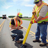 John Cross<br /> Minnesota Department of Transportation workers Kara Melvin and Randy Glaser install a plastic lane delineator on Highway 14 between Nicollet and North Mankato on Monday. This time, all 600 of the plastic tubes were screwed into the roadbed. Many of the devices that were installed last summer with adhesive had come loose during hot weather in mid-May.