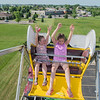 Elin Peterson (left), 5, looks at her friend Lynnea Kelly, 10, as the two rode the ferris wheel at the Greater Mankato Growth Business After Hours held at Farrish Johnson Law Offices on Tuesday. Photo by Jackson Forderer