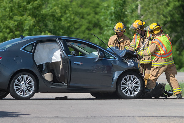 Eagle Lake fire fighters pry open the hood to a car that was involved in a two-car accident at the intersection of Highway 14 and 598th Avenue on Thursday. Photo by Jackson Forderer